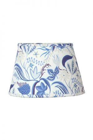 Lampskärm Indi Ljusblå Oval. Oval mönstrad lampskärm i ljusblå bomull. Mönstret är skapat av Joy Zandén. Skärmen levereras med klofäste. Skärmen finns i två storlekar och flera färger.