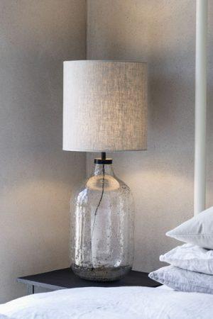Bordslampa Groove, Skärm Celyn Natur. Lampfoten är handgjord i ofärgat glas med bubblor och sandeffekter. Designen är inspirerad av gamla flaskor för att få en ruffkänsla och varje lampfot är unik. Lampfoten har svarta metalldetaljer och 2 meter lång svart sladd. Sockel E27. Leveras med naturfärgad skärm Celyn i polyester. Lampan finns i två olika storlekar på fot och skärm.
