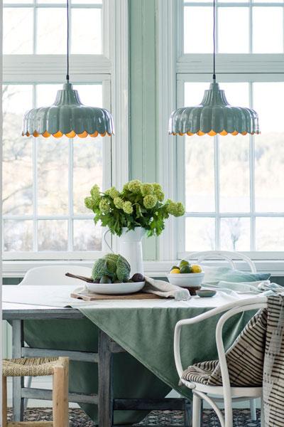 Taklampa Wells Vit. Wells är en fräsch romantisk serie som är inspirerad och skapad efter inspiration av en blomma. I serien finns taklampa, fönsterlampa och bordslampa i 4 färger, Rosa, grön, vit och svart. Alla har en guldfärgad insida som sprider ett varmt härligt sken. Varje skärm är handgjord. Wells kommer pryda ditt hem med sina feminina former och läckra färger.Lampan har 1,6 meter svart textilsladd och takkopp i samma färg som lampan. Sockel E27. 25W.