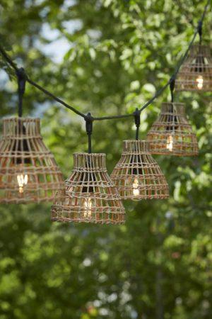 Ljusslinga Flex Out Sarah. Ljusslinga för utomhusbruk (IP44) med 5 st lamphållare. Totallängd 6,5 m, 2,5 m till första lamphållaren, sedan 80 cm mellan varje lamphållare. 15 cm från T-koppling ner till skärmring. Här matchat med 5 st Sarh lampskärm i naturmaterial. Skärmen är 18 cm bred och 18 cm hög.