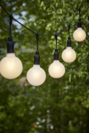 Ljusslinga Flex Out Pearl 125 mm. Ljusslinga för utomhusbruk (IP44) med 5 st lamphållare. Totallängd 6,5 m, 2,5 m till första lamphållaren, sedan 80 cm mellan varje lamphållare. 15 cm från T-koppling ner till skärmring. Här matchat med 5 st Opalvita LED lampfor. Lampan är 12,5 cm bred och 17 cm hög.