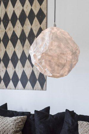 En lampa gjord av vaxat papper som med sin struktur ger ett effektfullt sken. Stängs med en dragkedja.